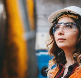 Portrait of young businesswoman with white helmet looking up and seen from the industrial steel cable reel for crane in factory warehouse. She is testing and working with winding wire and cable drum accessories metal wire spool reel wear resistance.